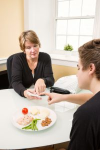 A Nutritionist counselling a teen diabetes patient about food choices and maintaining a healthy blood sugar level.